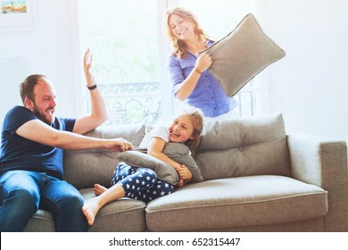 pillow fight at home, family playing together, parents laughing with daughter