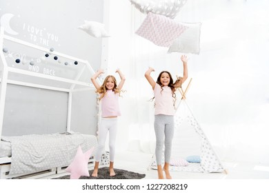 Pillow fight pajama party. Evening time for fun. Sleepover party ideas. Girls happy best friends or siblings in cute stylish pajamas with pillows sleepover party. Sisters play pillows bedroom party.