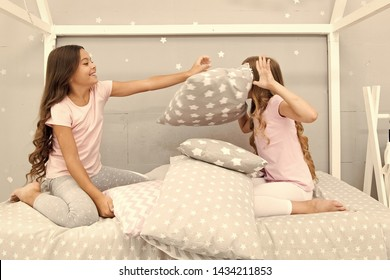 Pillow fight pajama party. Sleepover time for fun. Best girls sleepover party ideas. Soulmates girls having fun sleepover party. Girls happy best friends in pajamas with pillows sleepover party.