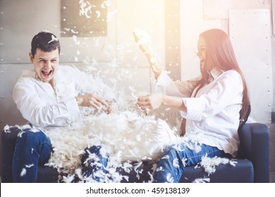Pillow fight. Young happy pregnant family have fun with fluffy feathers from pillow. Man and woman dressed in jeans and white shirts. Vintage color effect.