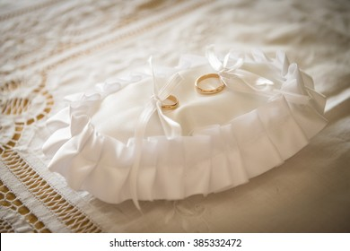 a pillow with golden wedding rings