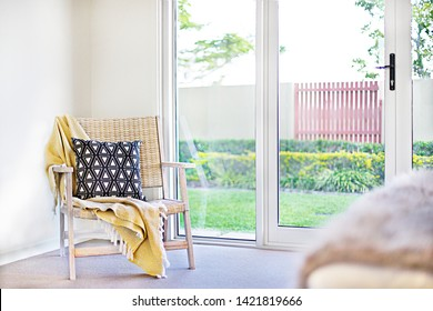 Pillow with a wooden chair and a yellow sheet beside a door to the outdoor garden view, including a sunlight illumination and green grass lawn near a gate, closed glass door inside front view
