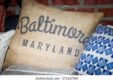 """Pillow with the words """"Baltimore, Maryland"""" in cursive and block writing surrounded by a blue and white printed pillow"""