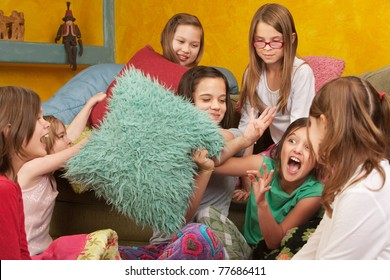Pillow-fighting among seven girls at a sleepover