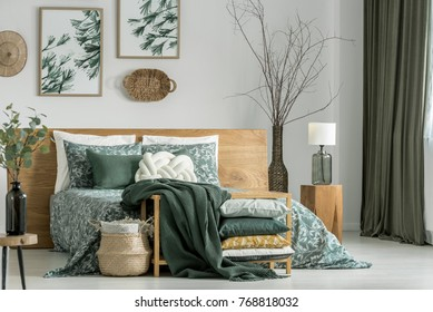 Pillows and blanket on cabinet in khaki bedroom with wooden furniture and white pillow on bed