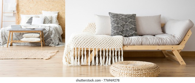 Pillows and knit blanket on wooden settee and pouf in multifunctional bedroom with king-size bed
