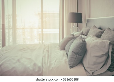 pillows on bed and luxury black lamp style on wooden table side in bedroom design, vintage process style