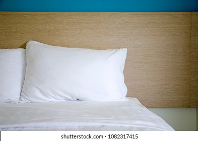 The pillows on the bed with white cover and wooden background.