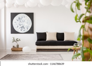 Pillows on black sofa in white living room interior with moon poster and grey carpet. Real photo