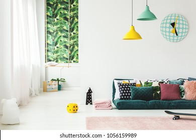 Pillows on emerald green mattress in kid's room interior with swing and clock on white wall
