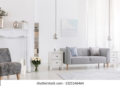 Pillows on grey settee in white living room interior with flowers near patterned armchair. Real photo