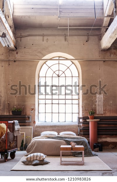 Pillows and table on carpet in front of bed in industrial bedroom interior with window and plant. Real photo