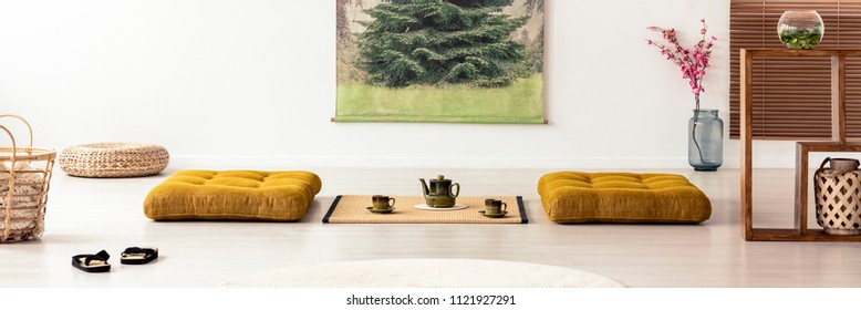 Pillows and tatami mat on the floor in japanese dining room interior with flowers. Real photo