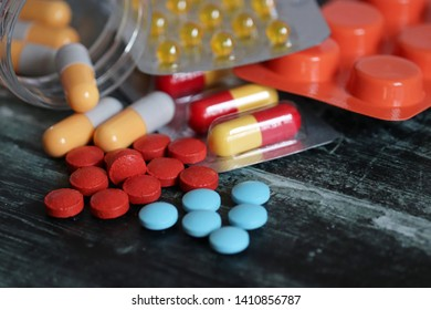Pills and capsules in blister pack and bottle on dark wooden table, different types of drugs close-up. Concept of pharmacy, vitamins, health care