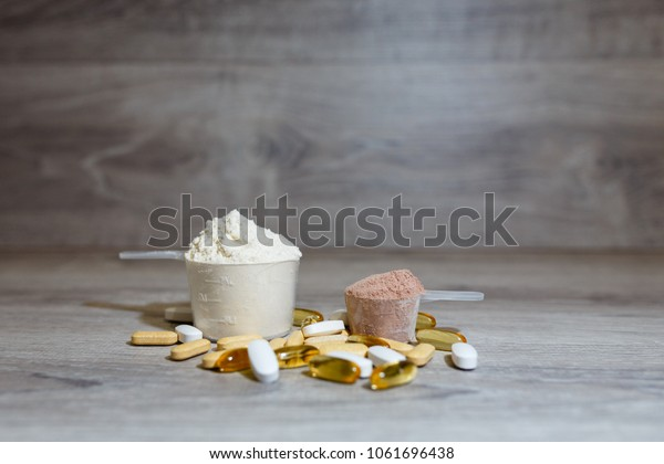 Pills and capsules of Omega 3, carnitine, creatine, fat burner, BCAA or testosterone booster. Sports medical vitamins. Two scoop of whey banana and chocolate protein on wooden background