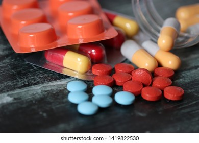 Pills and capsules on dark wooden table, a lot of multicolored medication close-up. Concept of pharmacy, vitamins, health care