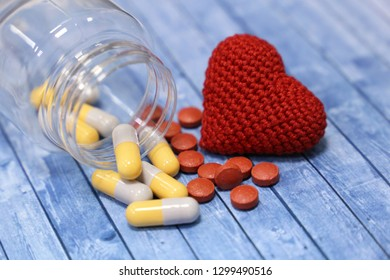Pills, capsules, red knitted heart and transparent plastic bottle on blue wooden table. Concept of treatment of heart disease, blood pressure, polypharmacy, anti-depressants, sedative