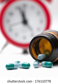 Pills  and clock  over white background,closeup, for health care,medicine,addiction themes