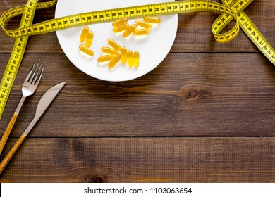 Pills or dietary supplement for weight loss. Treatment of obesity. Treatment of anorexia. Gold pills on plate near measuring tape on dark wooden background top view.