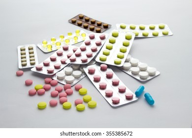 Pills of different colors on a light background