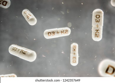 Pills float in the air with inscription D3 + K2 vitamins