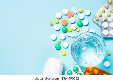 Pills and glass of water on blue background top view. Medical pharmacy concept.