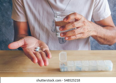 Pills and a glass of water on hand of man in health time