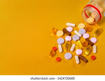 Pills from a jar on a gold background, close-ups of vitamins of different groups, such as vitamins A, B, C, E, D, Lutein + blueberries, Beta-Karatin + Sea-buckthorn, Black thyme oil, gathered,Omega 3.