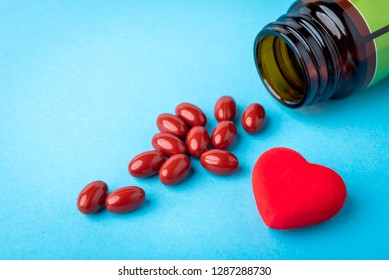 Pills from jar and red heart on blue background. Heart tablets. Coenzyme q10.