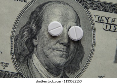 The pills lie in place of the eyes, on a bill of one hundred dollars close-up. The concept of insurance medecine, insurance, high cost, high cost of drugs.