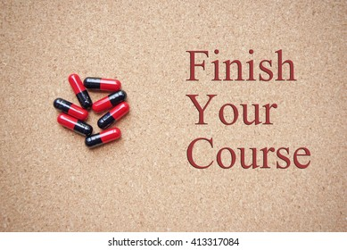 pills on a brown board. medical advice message. finish your course.