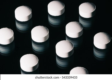 Pills on dark reflective surface