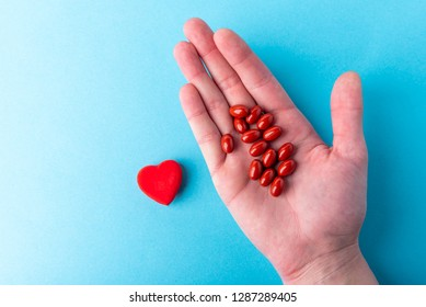 Pills on hand and red heart on blue background. Heart tablets. Coenzyme q10.