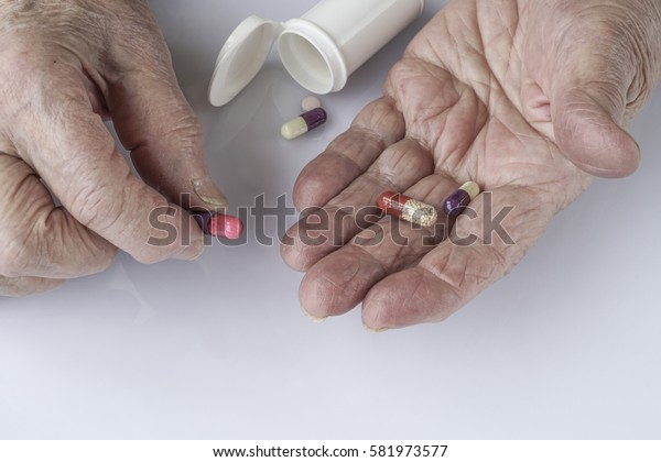 pills on palm of a senior person