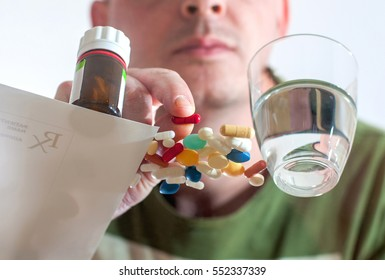 Pills on table and person taking a prescription pills with glass of water. Medication pills with prescription paper.