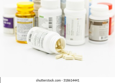 Pills on the white background with medicine bottle