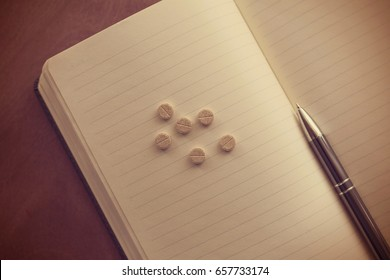 Pills paracetamol, aspirin or ibuprofen with notepad and pen