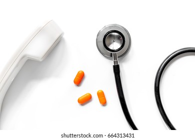 Pills with phone handset and phonendoscope on white background top view call doctor