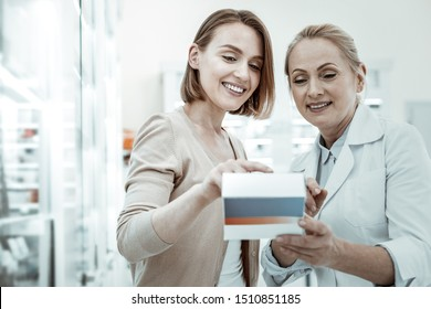 Pills prescription. A well-favoured smiling spouse attentively making study of pills prescription with a female mature apothecary worker in a white coat.