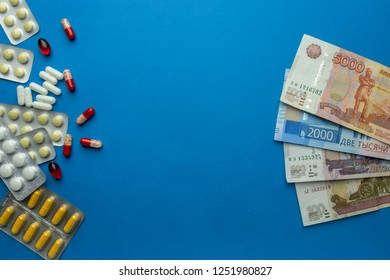 Pills with rubles money isolated on blue background. Medicine expenses. High costs of medication concept. Place for text