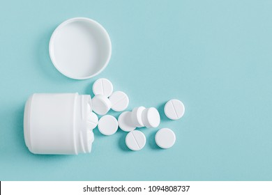Pills spilling out of pill bottle on blue background, top view