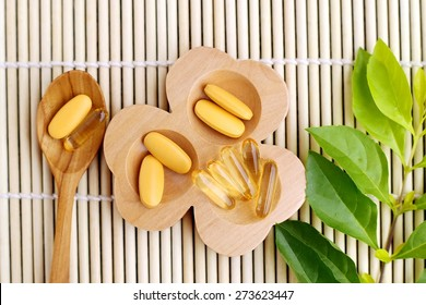 Pills and supplements in a wooden spoon
