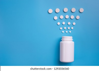 Pills, tablets and bottle on blue background. Copy space for text