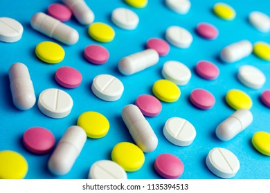 Pills tablets capsule drugs blue background. Medicine Pharmaceutical medicament concept.