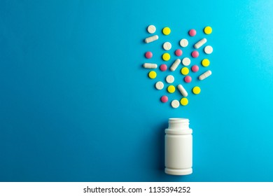 Pills tablets capsule plastic drugs bottle blue background. Drug prescription for treatment concept.