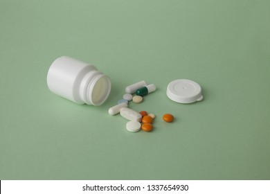 Pills, tablets and capsules and a bottle on a green background. Copy space for text.