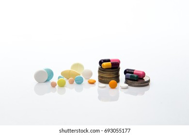 Pills, tablets and coins on white isolated background. Selective focus, shallow depth. Medical and health concept