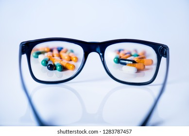 Pills, tablets focused in glasses on a black background. Pharmacy and medicine concept. Focused on a pharmaceutical industry. Different type of pills in blister,. Medicine and healthy
