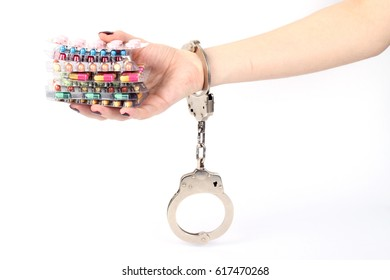 pills and tablets handcuffed hands on white background