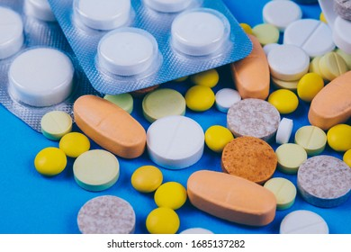 Pills and tablets on blue background.  Tablets in blisters.Various treatments mixed. Variety of pills and medication. Close up. Macro. Medical concept.